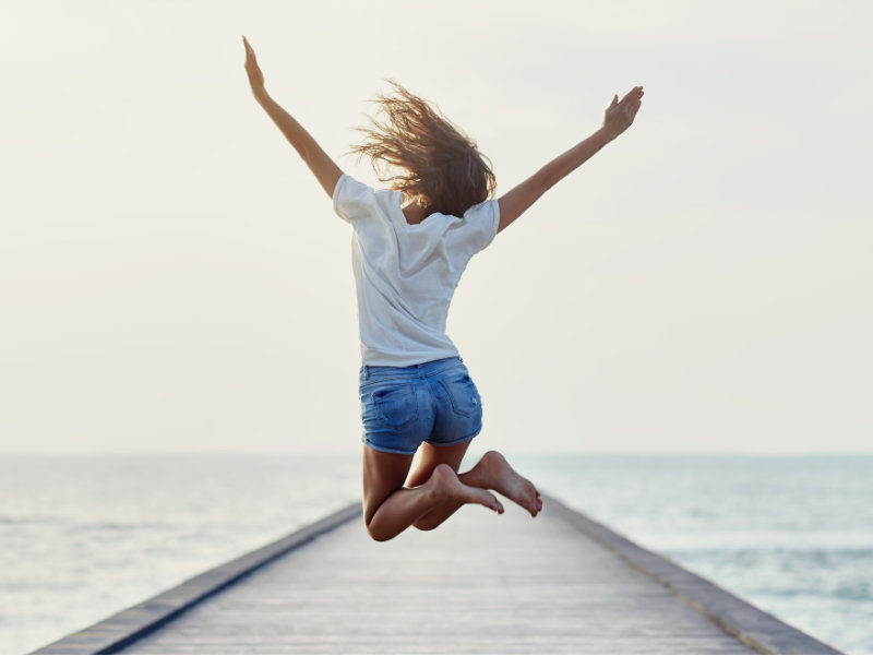 Girl jumping for joy on a pontoon leading to the sea