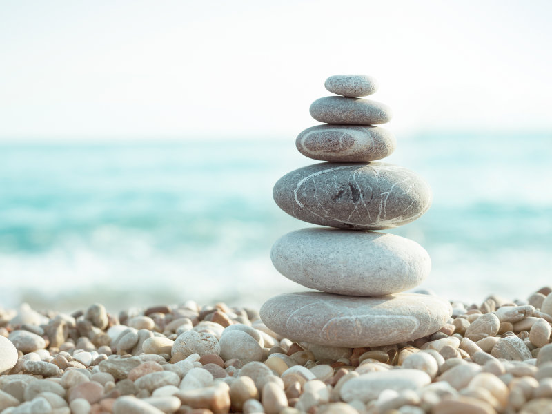 Pile of pebbles balanced on each other on a beach with a sea view background